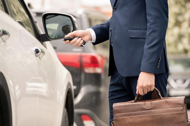 Junger zeitgenössischer geschäftsmann im anzug, der an seinem auto steht, während er die tür aufschließt und nach hause fährt