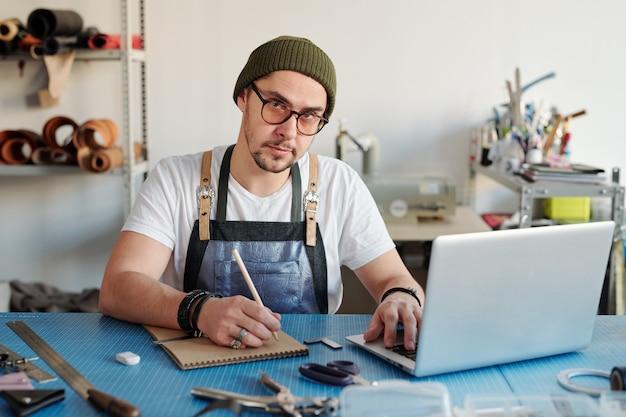 Junger zeitgenössischer lederarbeiter in der arbeitskleidung, die skizze von neuen gegenständen beim sitzen am tisch in der werkstatt macht