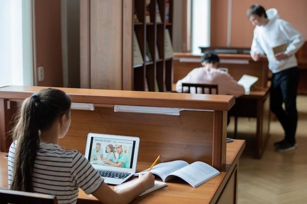 Junger zeitgenössischer student, der online-seite der bildungswebsite betrachtet, während notizen im notizblock in bibliothek macht