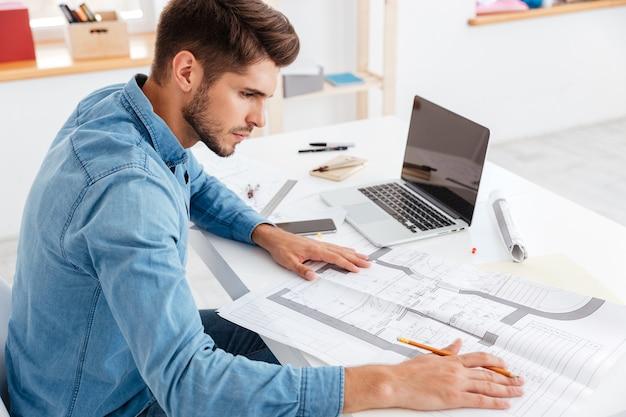 Junger zufälliger geschäftsmann, der mit dokumenten arbeitet, während er am bürotisch sitzt