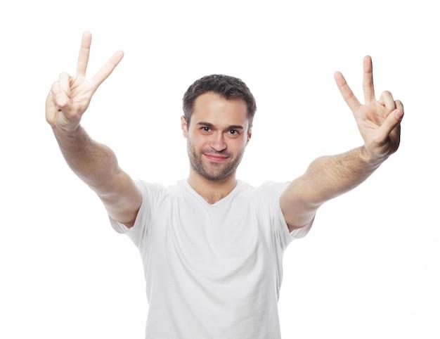 Junger zufälliger mann, der die siegesgeste zeigt, während er mit einer hand in der tasche für die kamera lächelt. isoliert auf weißem hintergrund