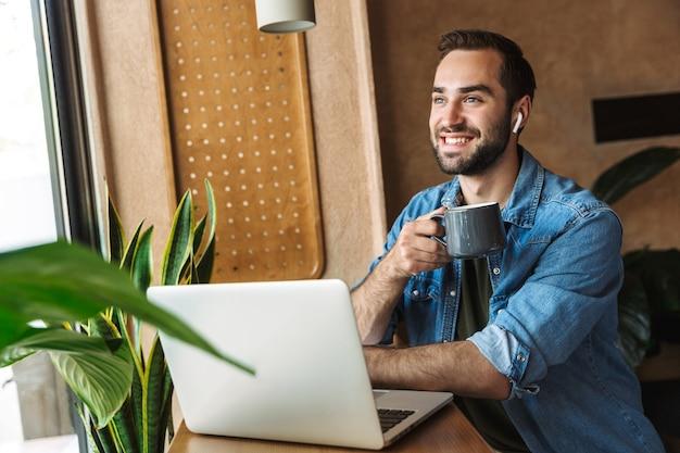 Junger zufriedener mann, der jeanshemd mit ohrstöpseln trägt und eine tasse kaffee mit laptop trinkt, während er im café drinnen arbeitet?