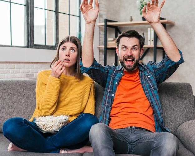 Junger zujubelnder mann beim aufpassen des matchfernsehens, das mit seiner frau sitzt