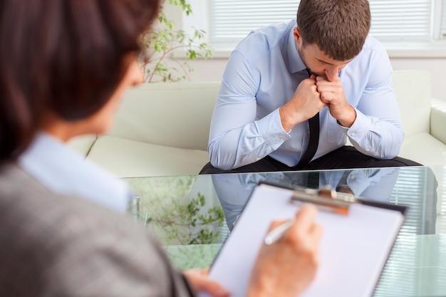Junger, zusammengebrochener mann, der depressionen beim psychotherapeuten heilt