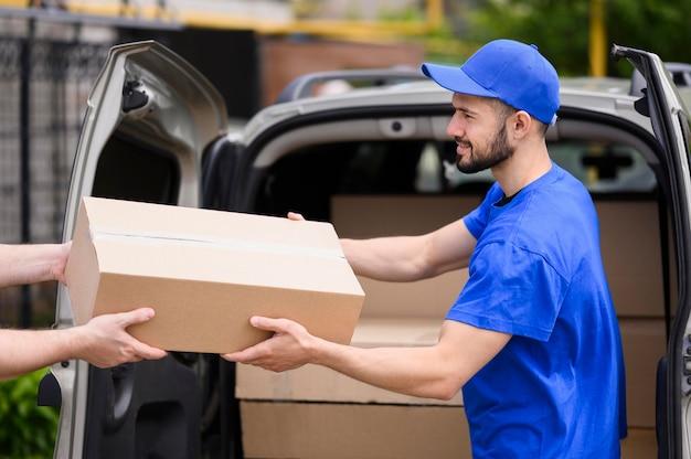 Junger zusteller, der paket zum kunden gibt
