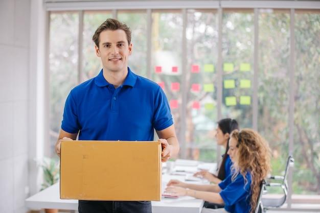 Junger zusteller, der paketpapierbox im zustellungsbüro hält.