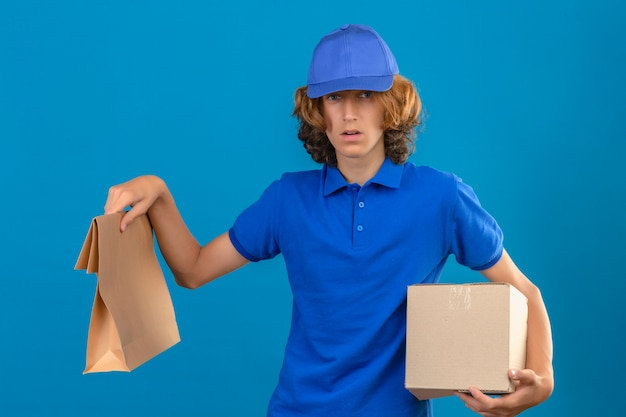 Junger zweifelhafter auslieferungsmann, der blaues poloshirt und kappe hält, die karton und papierpaket hält kamera mit zweifeln über isoliertem blauem hintergrund stehen