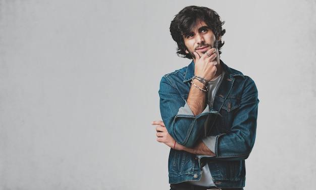 Junger zweifelhafter und verwirrter gutaussehender mann, denkend an eine idee oder besorgt über etwas