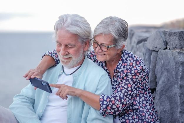 Junges älteres paar umarmt im freien auf see bei sonnenuntergang mit handy. kaukasischer ruhestand genießt entspannung und glücklichen lebensstil