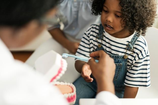 Junges afrikanisches kind mit einem zahnarzt