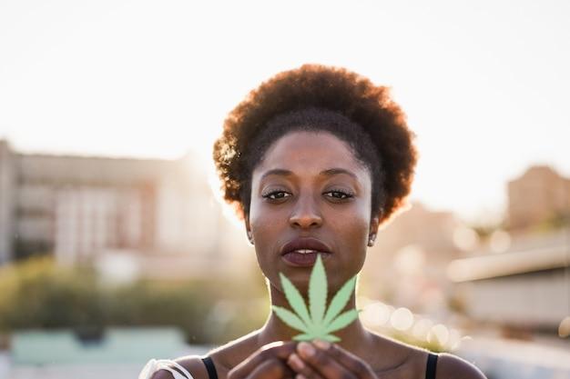 Junges afrikanisches mädchen, das marihuanablatt hält - fokus auf frauengesicht