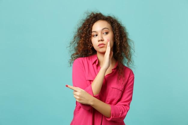Junges afrikanisches mädchen in freizeitkleidung, das geheimnis hinter ihrer hand flüstert, die den zeigefinger beiseite zeigt, einzeln auf blauem türkisfarbenem hintergrund. menschen aufrichtige emotionen lifestyle-konzept. kopieren sie platz.