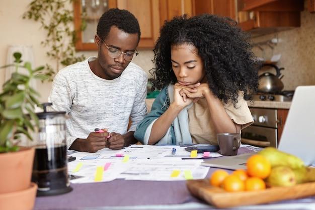 Junges afrikanisches paar, das papierkram zusammen macht und am küchentisch mit vielen papieren sitzt