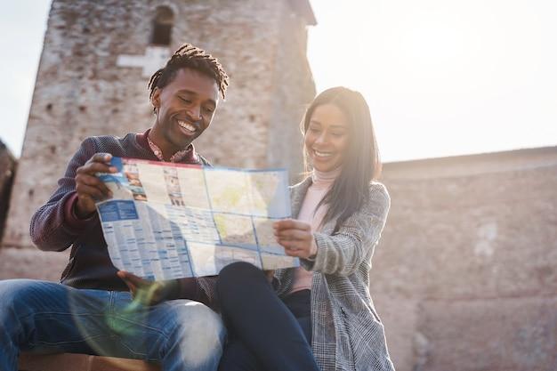 Junges afrikanisches paar hat spaß mit der karte während der ferien - fokus auf das gesicht des mannes