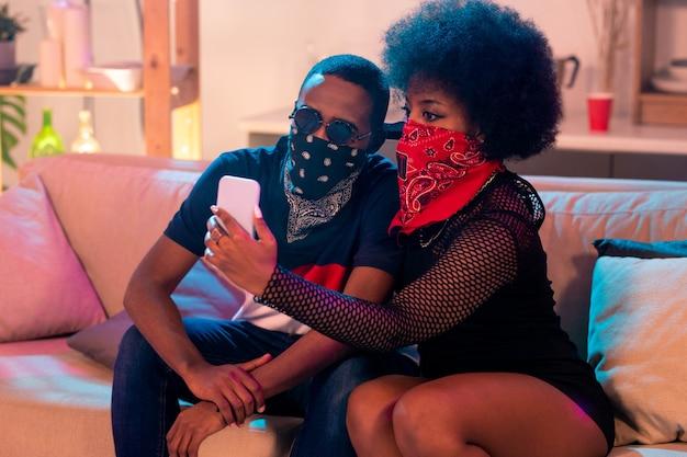 Junges afrikanisches paar in den bandanas des roten und schwarzen gesichts, die auf weicher couch sitzen und smartphone-kamera betrachten, während selfie machen