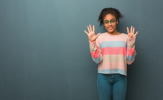 Junges afroamerikanermädchen mit blauen augen, die nummer neun zeigen