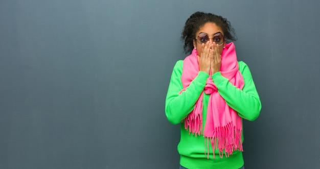 Junges afroamerikanermädchen mit blauen augen sehr ängstlich und ängstlich versteckt