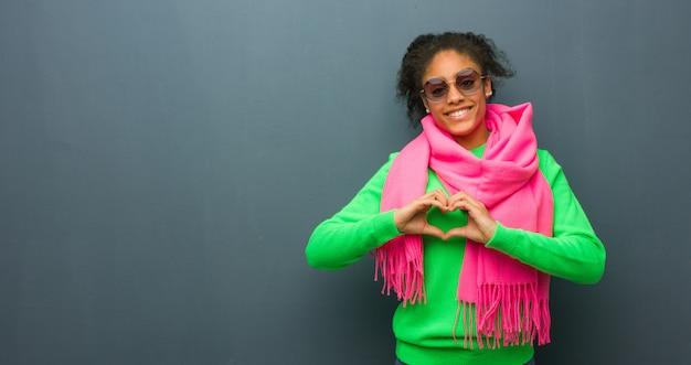 Junges afroamerikanermädchen mit den blauen augen, die eine herzform mit den händen tun