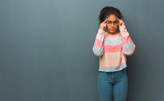 Junges afroamerikanermädchen mit den blauen augen, die eine konzentrationsgeste tun