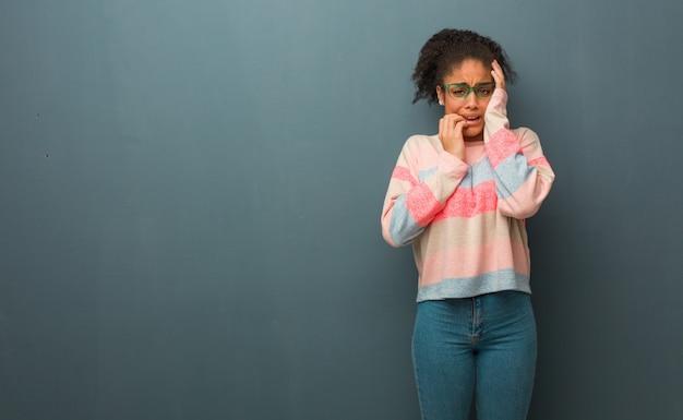 Junges afroamerikanermädchen mit den blauen augen hoffnungslos und traurig