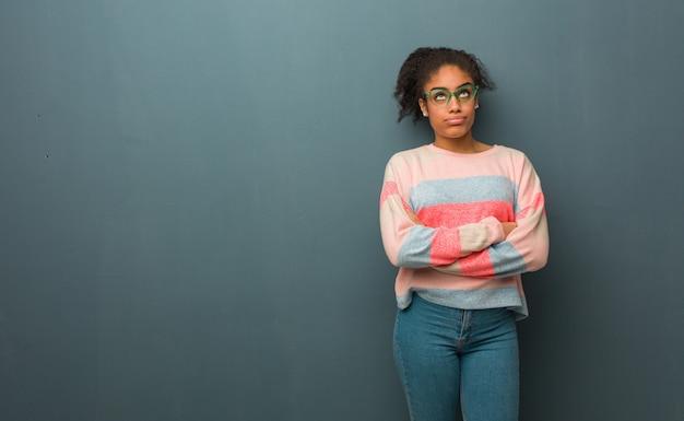 Junges afroamerikanermädchen mit den blauen augen müde und gelangweilt