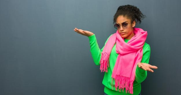Junges afroamerikanermädchen mit den blauen augen verwirrt und zweifelhaft