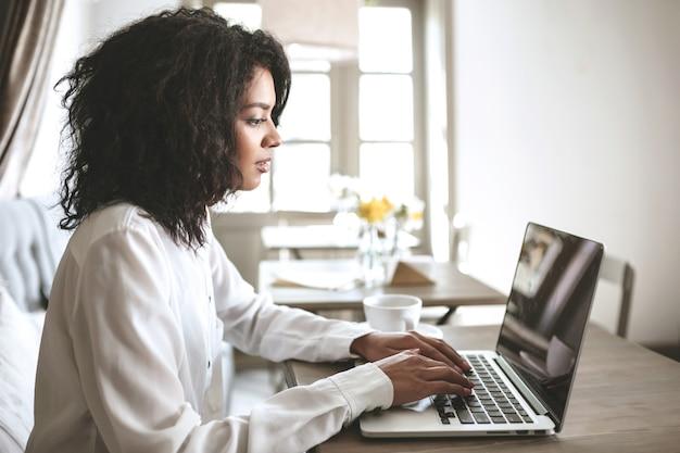 Junges afroamerikanisches mädchen, das an ihrem laptop im restaurant arbeitet. hübsche dame mit dunklem lockigem haar, das an café mit laptop sitzt