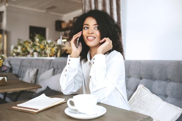 Junges afroamerikanisches mädchen, das im restaurant sitzt und auf ihrem handy spricht. mädchen mit dunklem lockigem haar, das im café mit tasse kaffee und menü auf tisch sitzt