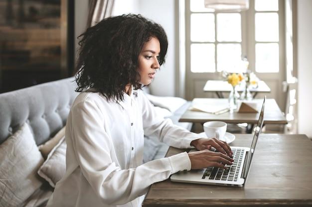 Junges afroamerikanisches mädchen, das im restaurant sitzt und auf ihrem laptop tippt. hübsches mädchen, das am computer am café arbeitet