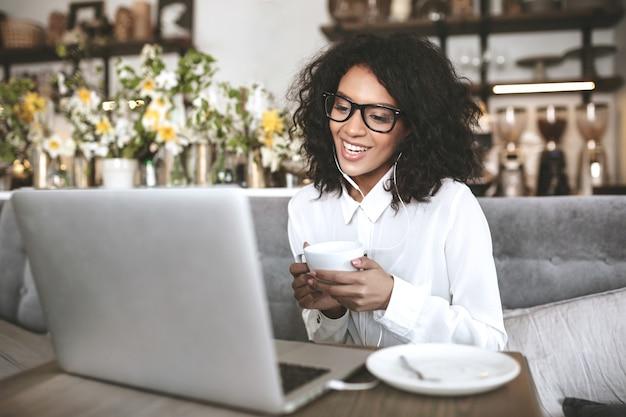 Junges afroamerikanisches mädchen in den gläsern, die im restaurant mit laptop und tasse kaffee in händen sitzen