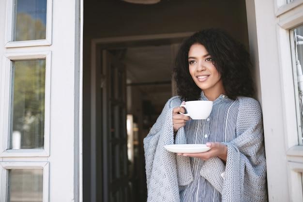 Junges afroamerikanisches mädchen mit dunklem lockigem haar, das kaffee trinkt, der an tür lehnt. schöne dame stehend mit tasse in der hand in plaid gewickelt