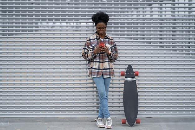 Junges afroamerikanisches mädchen scrollen durch soziale medien im handy, das chat über drahtloses internet eintippt