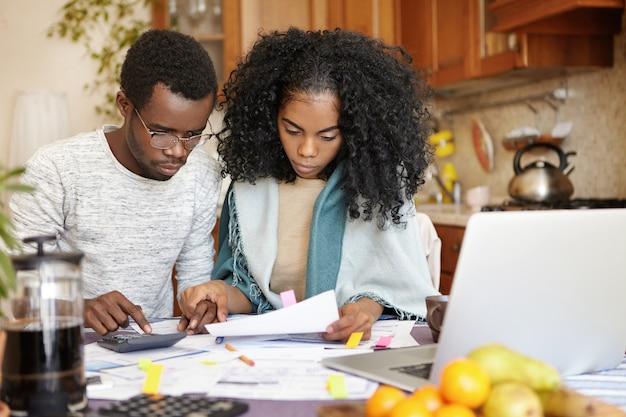 Junges afroamerikanisches paar, das finanzen zusammen zu hause verwaltet