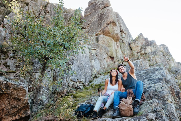 Junges aktives paar, das blick von der spitze eines berges genießt und finger zeigt