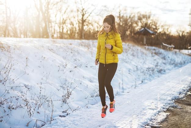 Junges aktives sportliches mädchen, das in wintersportbekleidung auf verschneiter winterstraße mit kopfhörern im sonnigen morgen joggt.