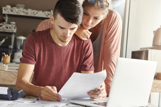 Junges amerikanisches paar, das rechnungen online unter verwendung des laptops zu hause berechnet