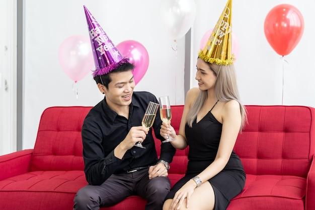 Junges asiatisches erwachsenes paar, das geburtstag mit sekt zusammen im wohnzimmer der großen eigentumswohnung in der großstadt feiert