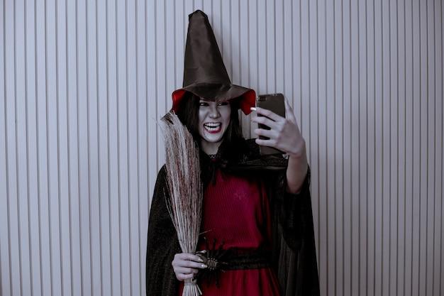 Junges asiatisches frauenkostüm in der schwarzen hexe mit hand, die besen und handy mit selfie an wand mit konzept für halloween-modefest hält.