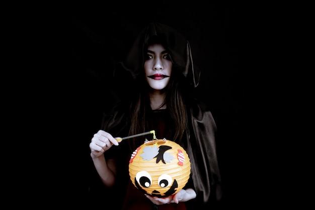 Junges asiatisches frauenkostüm in der schwarzen hexe mit hand, die einen orange halloween-kürbis auf schwarzer wand mit konzept für halloween-modefest hält.