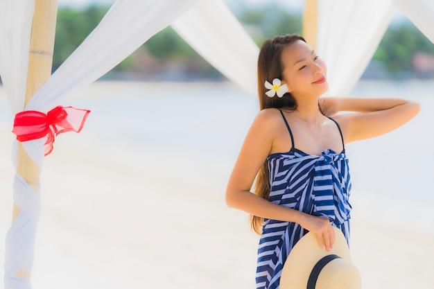 Junges asiatisches frauenlächeln des porträts glücklich um strandseeozean mit kokosnusspalme für feiertagsferien