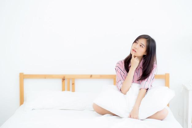 Junges asiatisches frauenlächeln des schönen porträts überzeugtes denken beim aufwachen