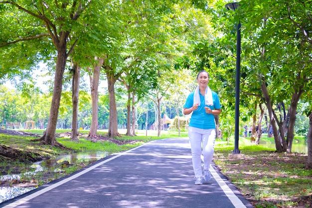 Junges asiatisches frauenportrait. sie joggt im park. sie lächelt und sei rechtzeitig glücklich