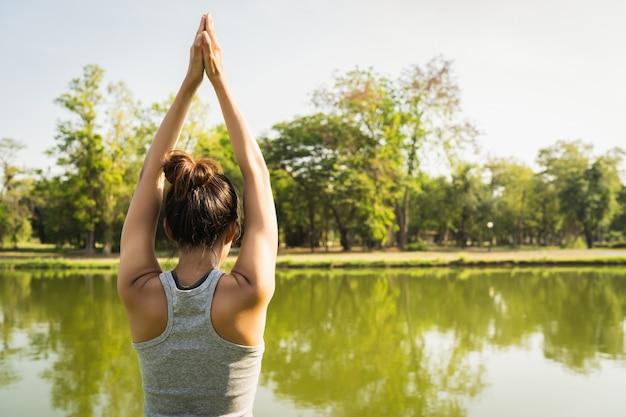 Junges asiatisches frauenyoga draußen halten ruhig und meditieren beim üben von yoga
