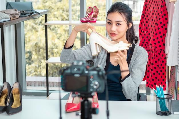 Junges asiatisches freundliches mädchen live videoblog (vlogger) und verkaufsschuhe beim online-e-commerce-einkauf im shop.