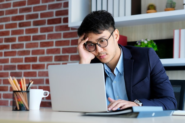 Junges asiatisches geschäftsmannkonzentrat auf dem arbeiten mit laptop-computer im büro, asiatischer büromann comtemplate auf dem arbeiten mit laptop-computer geschäftsleuten und bürolebensstil