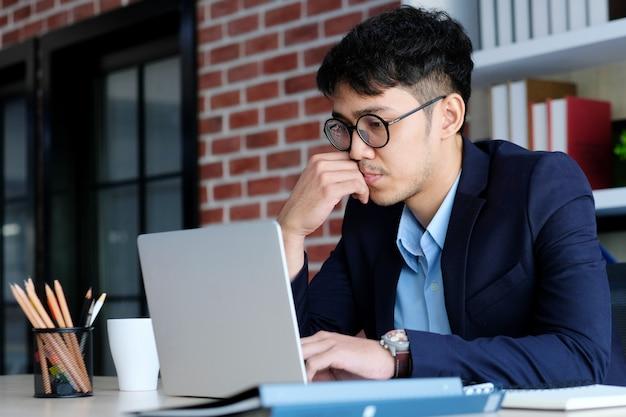 Junges asiatisches geschäftsmannkonzentrat auf dem arbeiten mit laptop-computer im büro, in den geschäftsleuten und im bürolebensstil