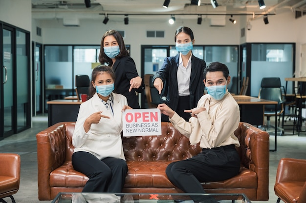 Junges asiatisches geschäftsteam, das gesichtsmaske mit plakat offenes geschäft als neue normalität auf ledersofa trägt