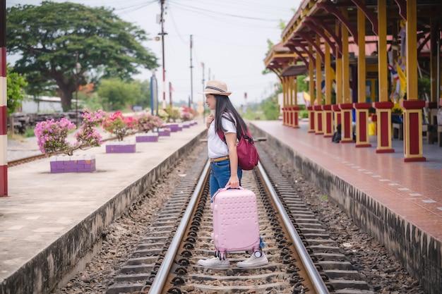 Junges asiatisches gril, das an der bahnstation vor reise geht. arbeits- und reisekonzept.