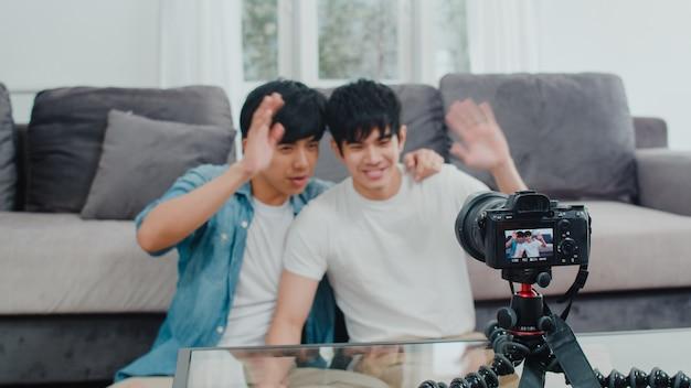 Junges asiatisches homosexuelles paarinfluencer-paar vlog zu hause. die jugendlich koreanischen glücklichen lgbtq-männer entspannen sich spaß unter verwendung des kameraaufzeichnungs-vlog-video-uploads in social media beim lügensofa im wohnzimmer am haus.