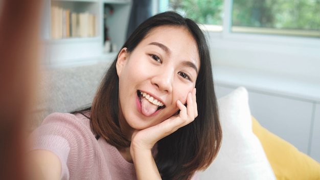 Junges asiatisches jugendlichfrau vlog zu hause, weiblich unter verwendung des smartphone, der dem social media vlog-video im wohnzimmer macht. lebensstilfrau entspannen sich am konzept des morgens zu hause.